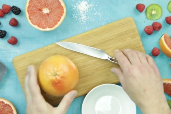 photo of a person cutting a grapefruit